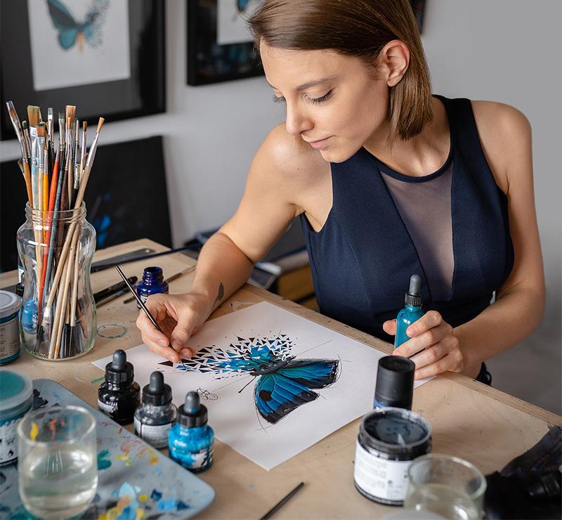 SAbrina Beretta peint dans son atelier un de ses effet Papillon