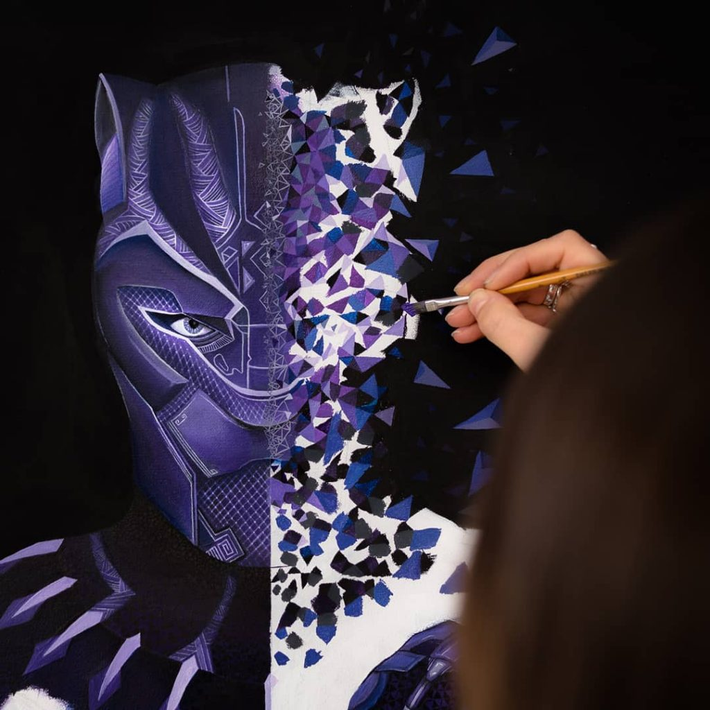 Sabrina Beretta en train de peindre Black Panther à l'acrylique